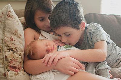 Siblings looking at baby boy while sitting on sofa - p1166m1414649 by Cavan Images