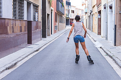 Rear view of teenage girl inline skating on road amidst buildings - p1166m1561526 by Cavan Images