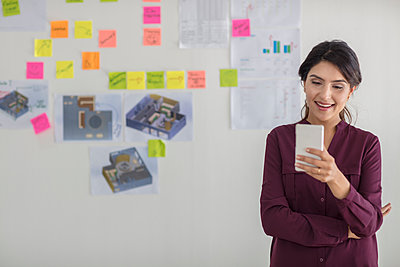 Happy businesswoman in office looking at cell phone - p300m1562614 by zerocreatives