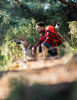 Thoughtful man with backpack crouching by dog in forest - p300m2293536 by Jose Carlos Ichiro