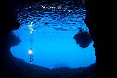 Diver at the entrance to a cavern off the island of Gato, Bohol Sea, Philippines - p442m1578804 by Dave Fleetham