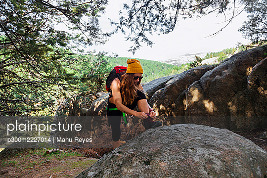 Trekker tying shoe lace while standing in forest at La Pedriza, Madrid, Spain - p300m2227014 by Manu Reyes