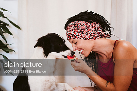 Woman smiling while feeding fruit to dog while sitting at home - p300m2251219 by Eva Blanco