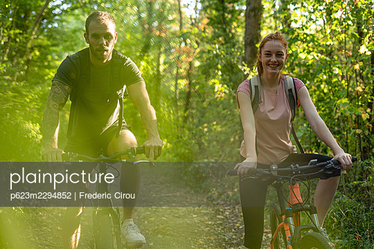 Smiling young couple cycling in forest - p623m2294852 by Frederic Cirou
