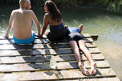 Family relaxing on dock at sunny riverside - p1023m2073965 by Sam Edwards