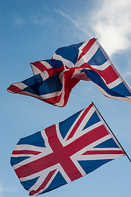 Two Union Jack flags blowing in the wind against a blue sky - p1047m1041662 by Sally Mundy