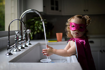 Portrait of girl wearing superhero costume washing hands in kitchen sink while standing at home - p1166m2067539 by Cavan Images
