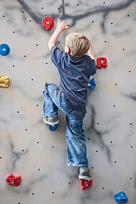 young boy climbing on indoor bouldering wall - p1166m2290336 by Cavan Images