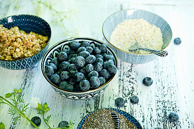 Bowls of blueberries, black chia seeds, granola and amaranth - p300m2023689 von Achim Sass