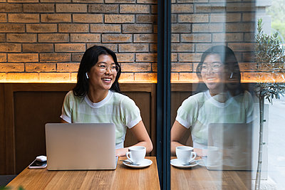 Young woman with laptop looking away while sitting near glass window at cafe - p300m2282770 by NOVELLIMAGE