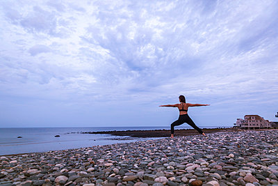 Warrior 2 yoga pose at sunset on beach - p343m1443486 by Lucie Wicker
