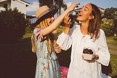 Beste Freundinnen essen Kirschen im Garten - p432m2260278 von mia takahara