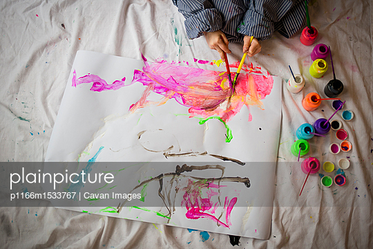 High angle view of boy painting on paper while sitting at home - p1166m1533767 by Cavan Images