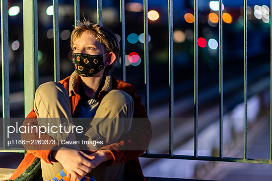 Teen with mask looking distant sitting against rail over train tracks - p1166m2269373 by Cavan Images