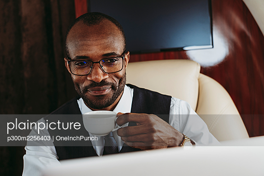 Smiling businessman with coffee cup in private jet - p300m2256403 by OneInchPunch