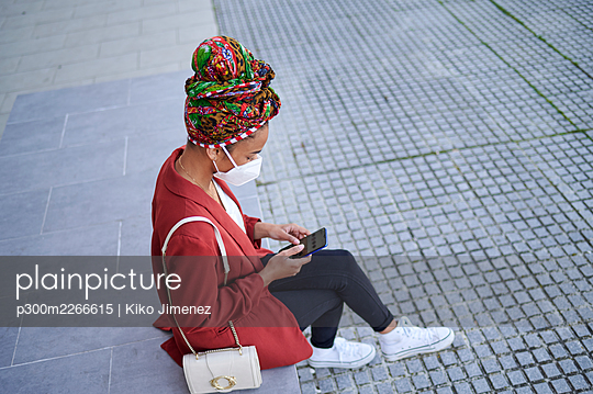 Spain, Andalusia, Jerez, woman with mask and headscarf using mobile phone in the street. - p300m2266615 von Kiko Jimenez