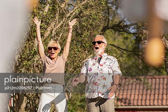 Happy senior couple in garden - p312m2208257 by Plattform