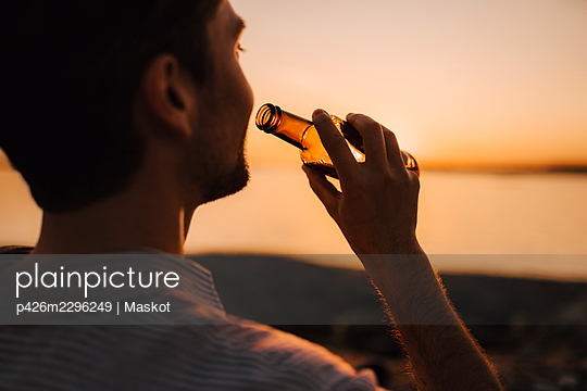 Man with beer bottle during sunset - p426m2296249 by Maskot