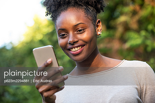 Close-up of smiling young woman using smartphone in park - p623m2294881 by Eric Audras