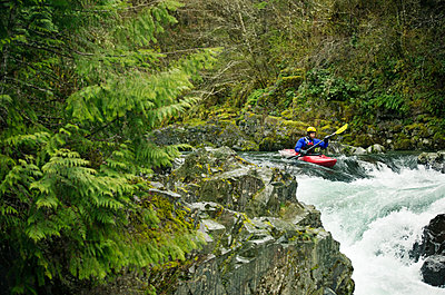 Man kayaking through waterfall in forest - p1166m1534045 by Cavan Images