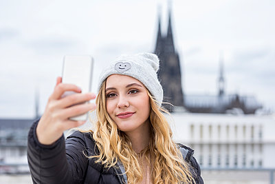 Germany, Cologne, portrait of smiling young woman taking selfie with smartphone - p300m1535642 by Jo Kirchherr