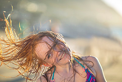 Girl on the beach smiling and swinging her hair in the wind - p300m998372f by zerocreatives