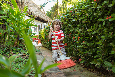 Caucasian boy playing with broom on path near house - p555m1305362 by Marc Romanelli