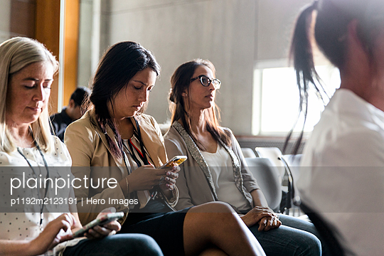 Businesswomen using smart phones in conference audience - p1192m2123191 by Hero Images