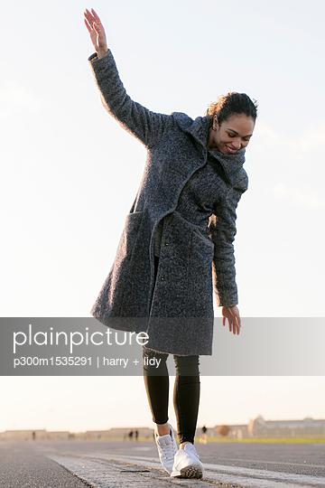 plainpicture | Photo library for authentic images - plainpicture p300m1535291 - Happy young woman walking o... - plainpicture/Westend61/harry + lidy