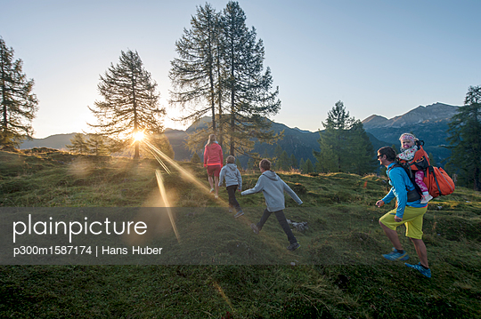 Family hiking in alpine meadow at sunset - p300m1587174 von Hans Huber
