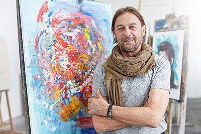 Portrait smiling, confident artist standing at abstract painting in art class studio - p1023m1506481 by Rafal Rodzoch