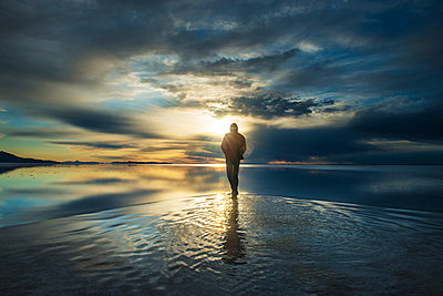 Full length of man standing on salt flat against cloudy sky during sunset - p1166m1186720 by Cavan Images