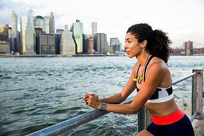 Thoughtful female athlete standing by river against sky in city - p1166m2000546 by Cavan Images