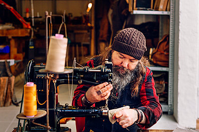 Male worker sewing bag pocket in workshop - p1185m994142f by Astrakan