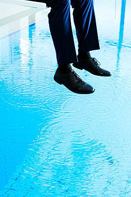 Geschäftsmann auf einem Sprungbrett im Schwimmbad - p1271m1548331 von Maurice Kohl