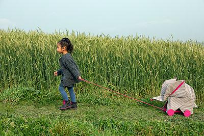 Little girl pulling origami elephant on rolls at field - p300m2012939 von Petra Stockhausen