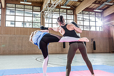 Female kickboxers practising in sports hall - p300m2144503 von Stefanie Baum