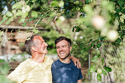 Father looking at tree while standing with son in backyard - p300m2275061 by Gustafsson