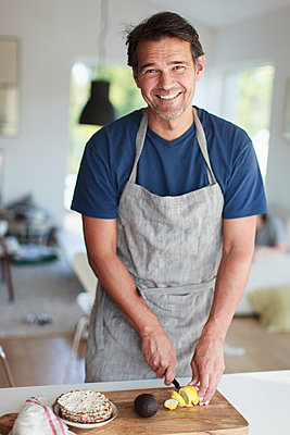 Portrait of smiling man cutting lemon in kitchen - p312m1533534 by Christina Strehlow