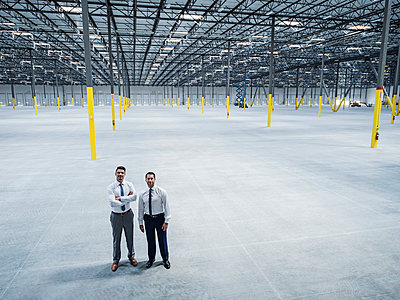 Smiling businessmen posing in empty warehouse - p555m1305135 by Erik Isakson