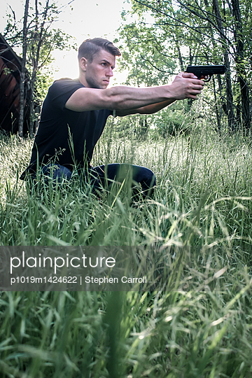 Man aiming with pistol  - p1019m1424622 by Stephen Carroll
