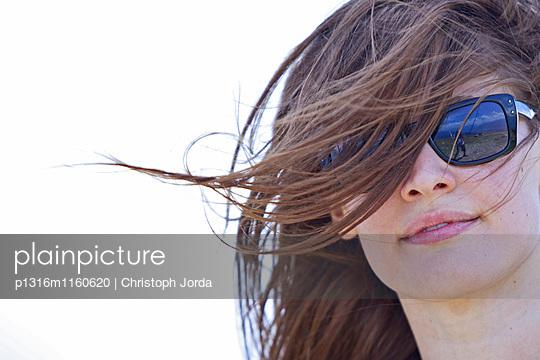 Jungen Frau mit Sonnenbrille lächelt in die Kamera, Nockberge, Kärnten, Österreich - p1316m1160620 von Christoph Jorda