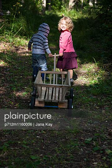 Kinder mit dem Bollerwagen im Wald - p712m1160006 von Jana Kay