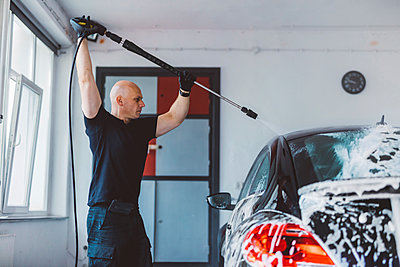 Confident worker pouring water on car with hose in workshop - p1166m2060367 by Cavan Images