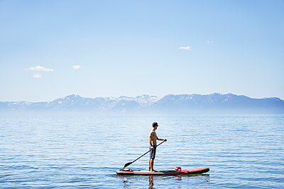 Side view of shirtless man paddleboarding on lake against blue sky during sunny day - p1166m2066959 by Cavan Images