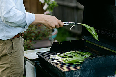 A man's hand putting seasoned wild ramps on the grill - p1166m2279308 by Cavan Images