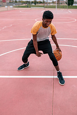 Teenager playing basketball - p300m2160533 by LUPE RODRIGUEZ