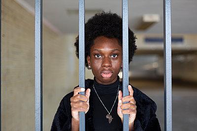 Deutschland, Berlin, Junge dunkelhäutige Frau in der S-Bahnstation vor Gitterstäben, Portrait - p975m2247765 von Hayden Verry