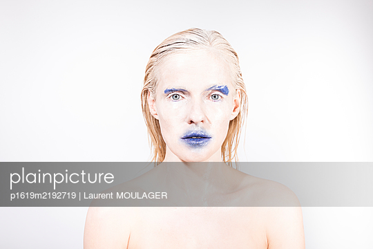 Portrait of a young woman with strange blue make-up facing camera - p1619m2192719 by Laurent MOULAGER