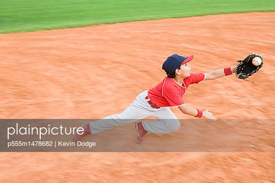 Hispanic baseball player catching ball